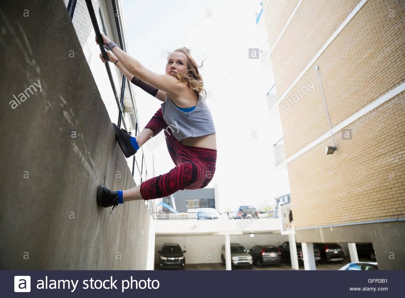 Giovane donna fare parkour lungo la parete urbana Immagini Stock