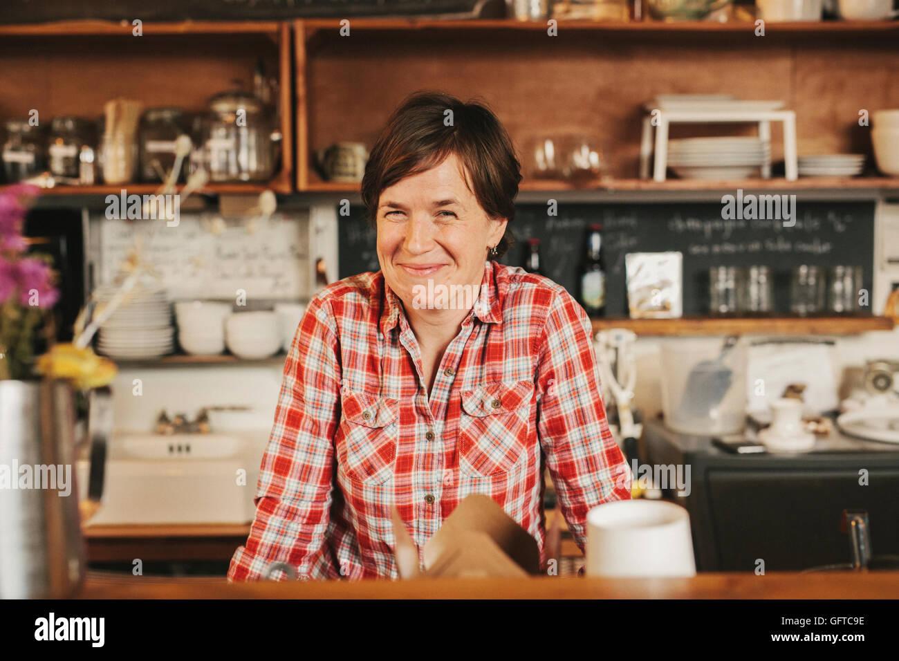Una donna che lavorano dietro il bancone in una caffetteria titolare di azienda Immagini Stock