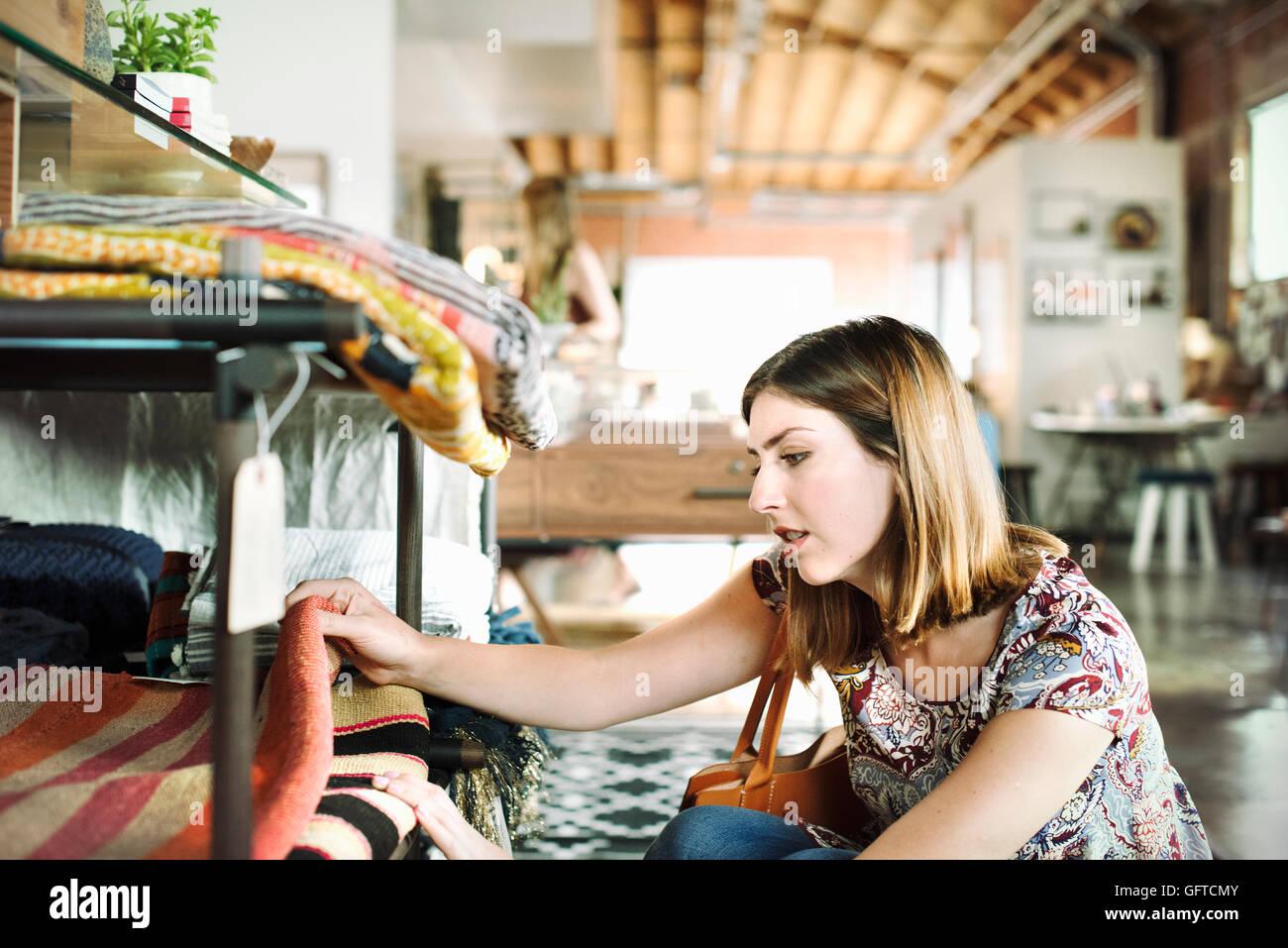 Giovane donna in un negozio guardando tappeti su un ripiano Immagini Stock