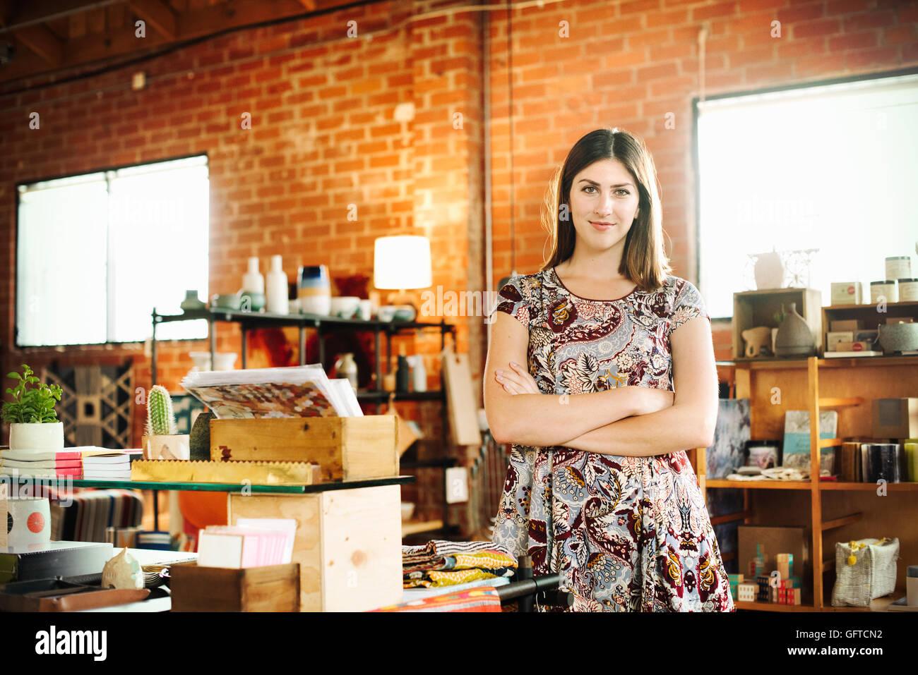 Giovane donna con capelli castani in piedi in un negozio di sorridere alla telecamera Immagini Stock