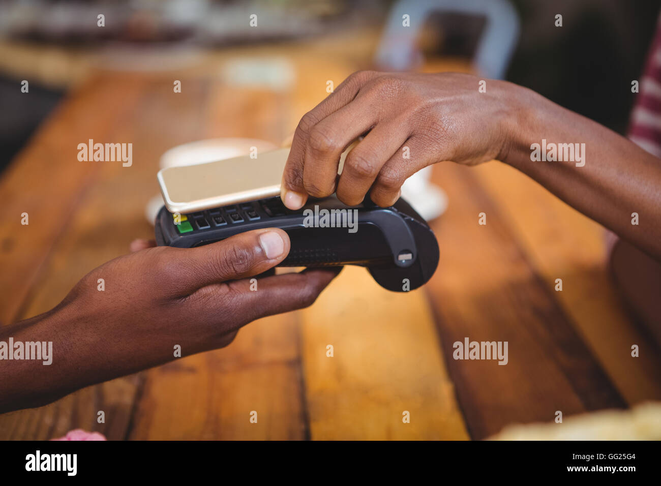 La donna il pagamento fattura tramite lo smartphone utilizzando la tecnologia NFC Immagini Stock