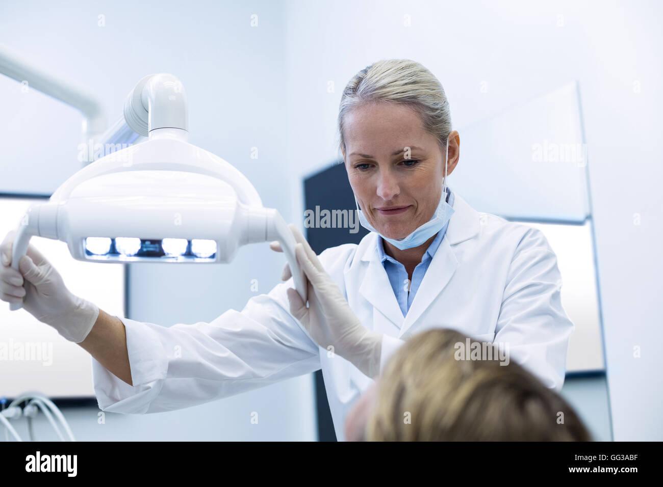 Dentista femmina regolazione luce dentale Immagini Stock