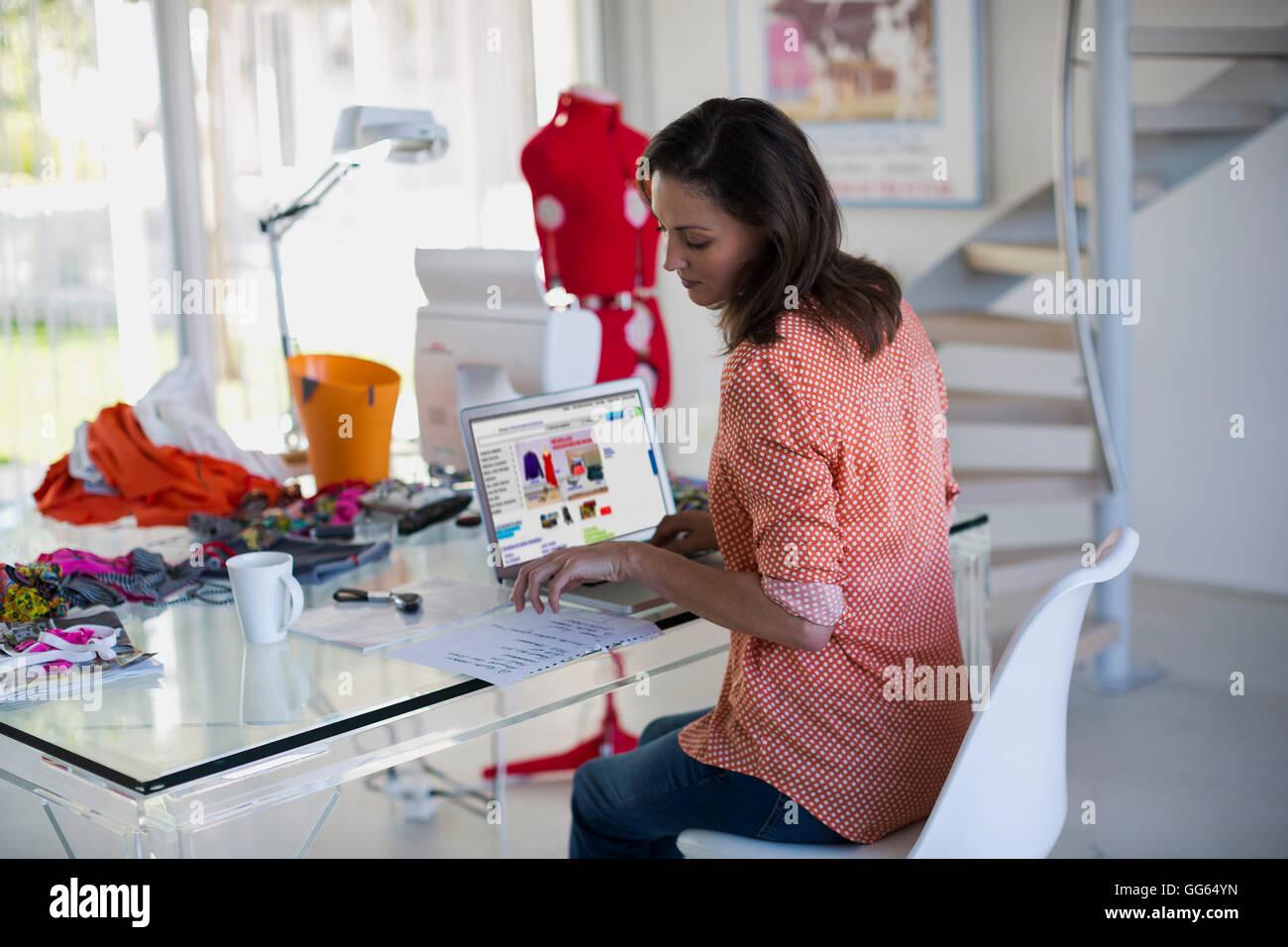 Fashion designer che lavora sul computer portatile nel suo ufficio Immagini Stock