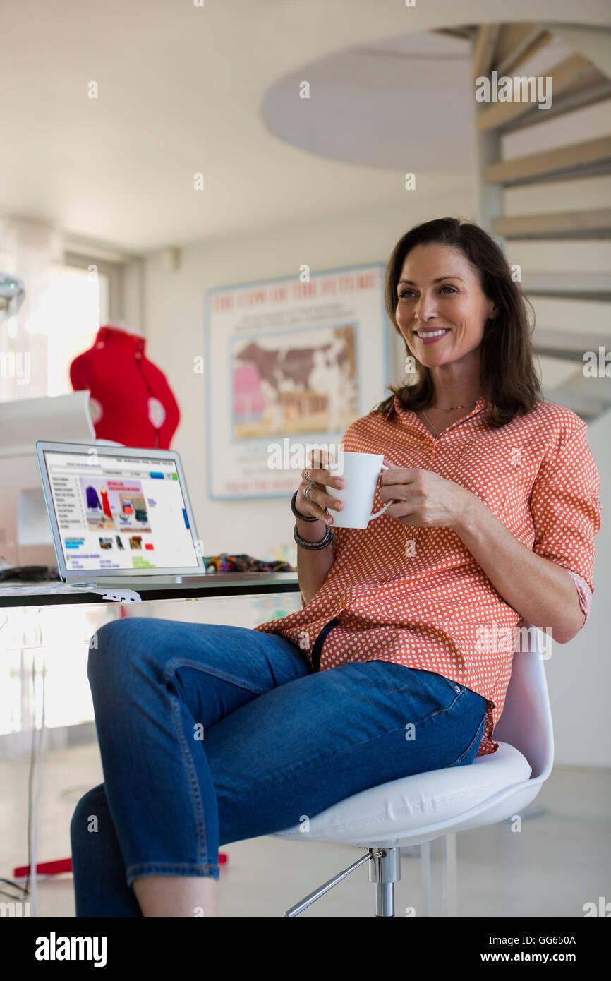 Felice dress designer di bere il caffè in ufficio Immagini Stock