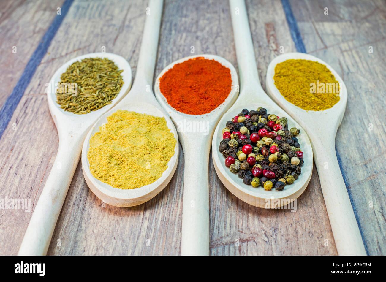 Colore variabile spezie esotiche sul cucchiaio di legno Immagini Stock