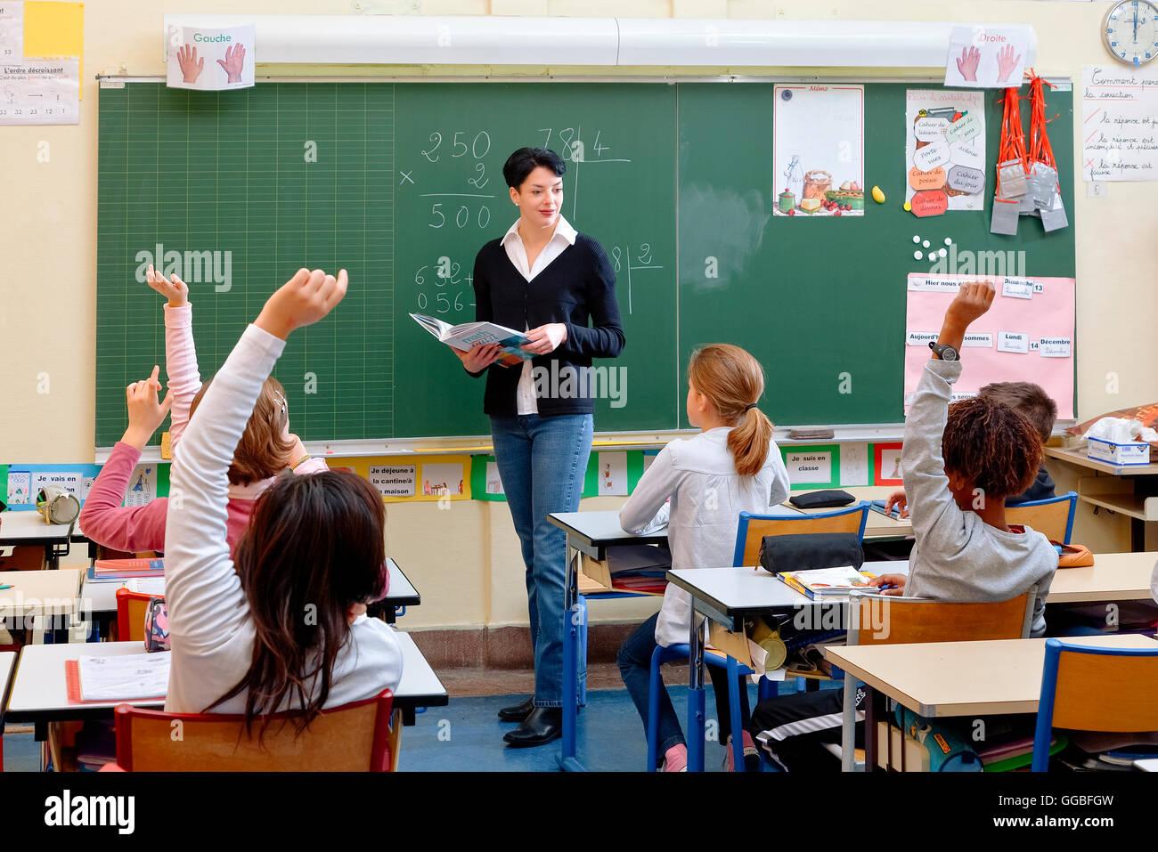 Ritratto di schoolkids diligente e la loro insegnante parlando a lezione Immagini Stock