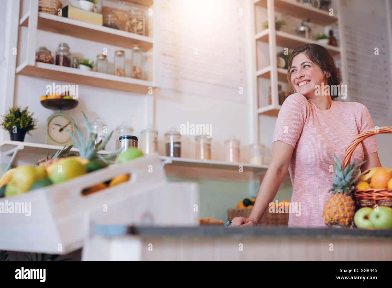 Ritratto di giovane e bella donna in piedi dietro il bancone del suo bar con succhi. Femmina caucasica lavorando Immagini Stock