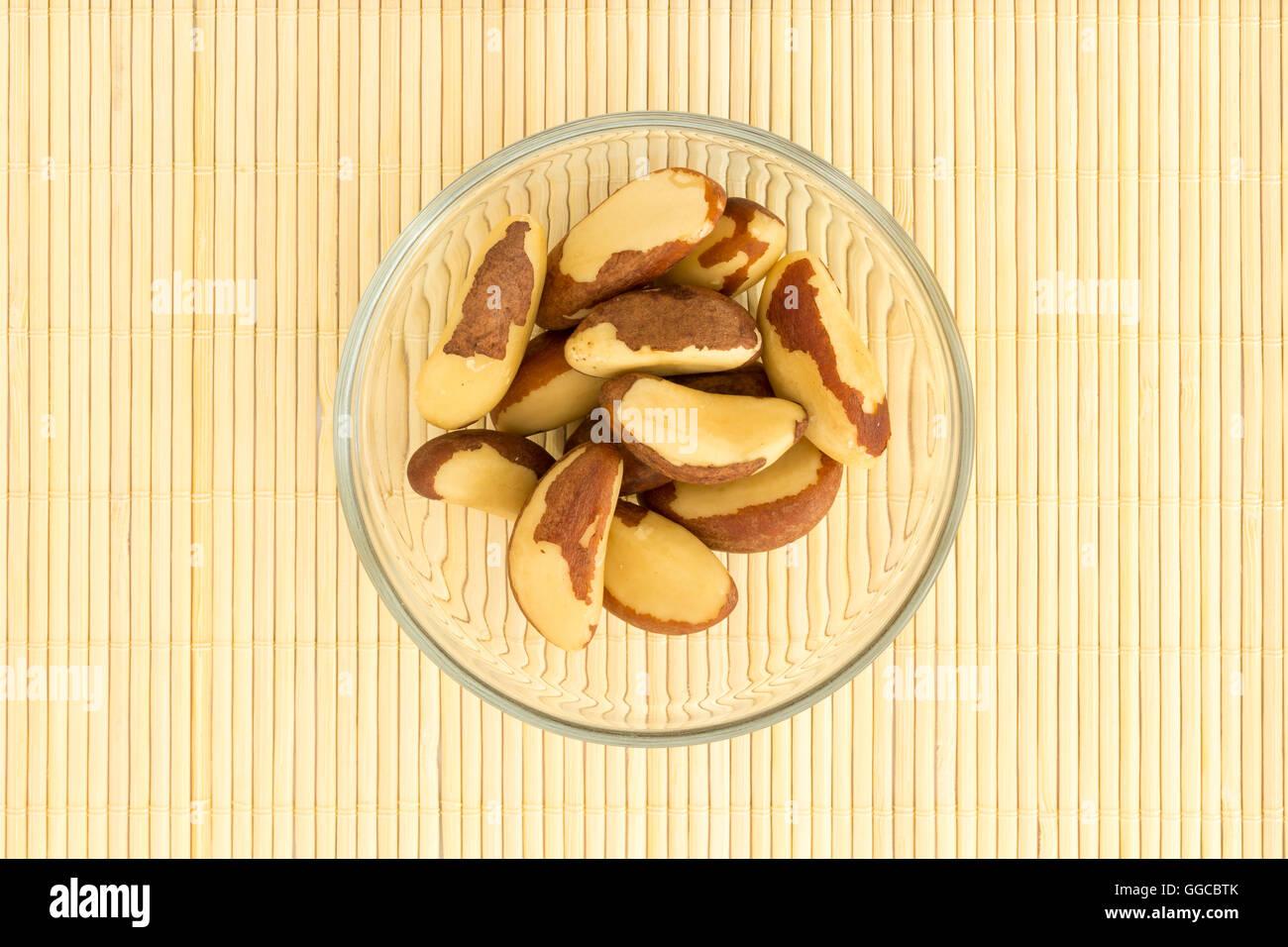 Vaso di vetro con le noci del Brasile su bambo mat. Questo dado è una ricca fonte di selenio e antiossidante Immagini Stock
