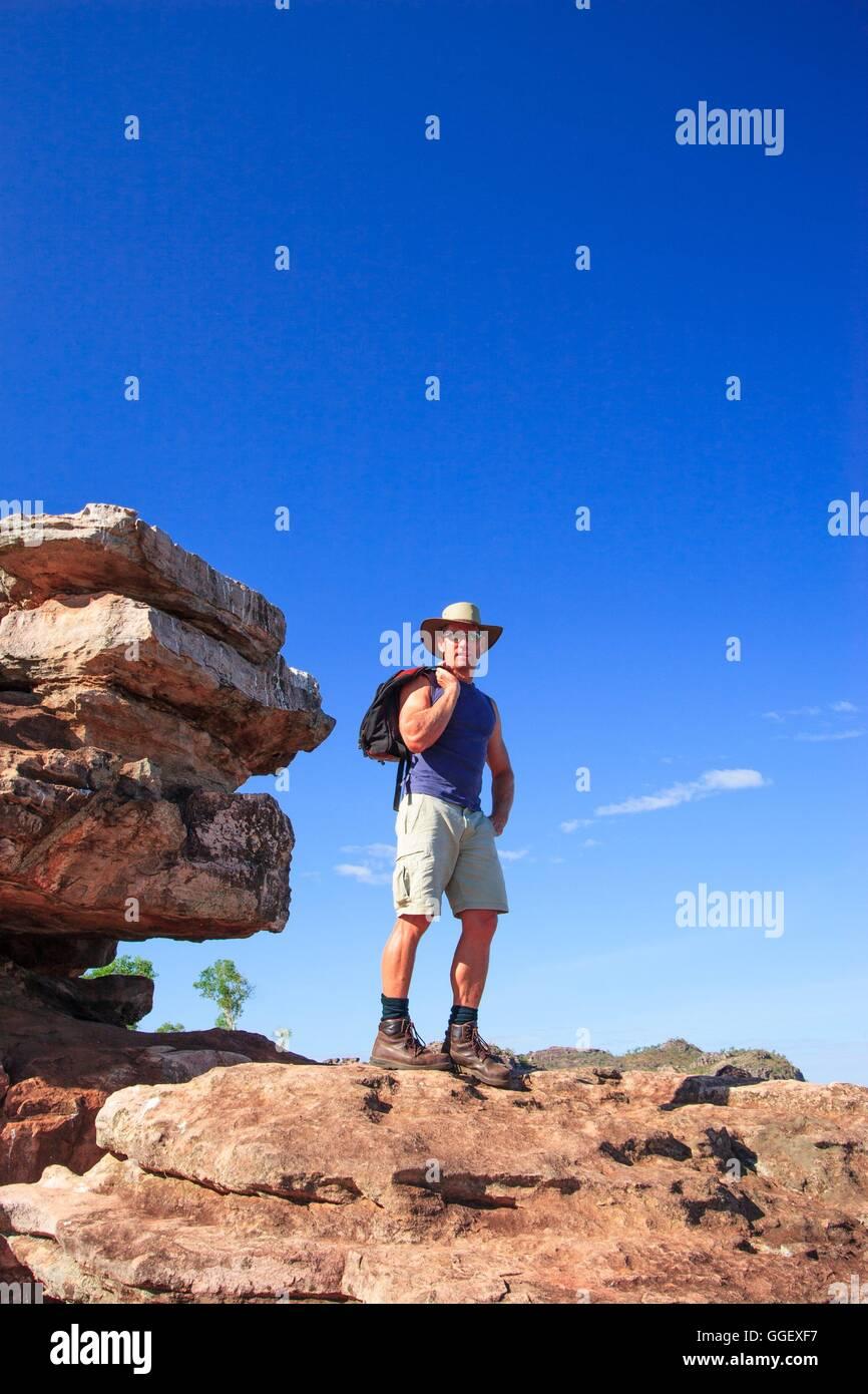 Un viaggiatore sorge sulla sommità di un ampio sperone roccioso in Arnhemland, Territorio del Nord, l'Australia. Immagini Stock