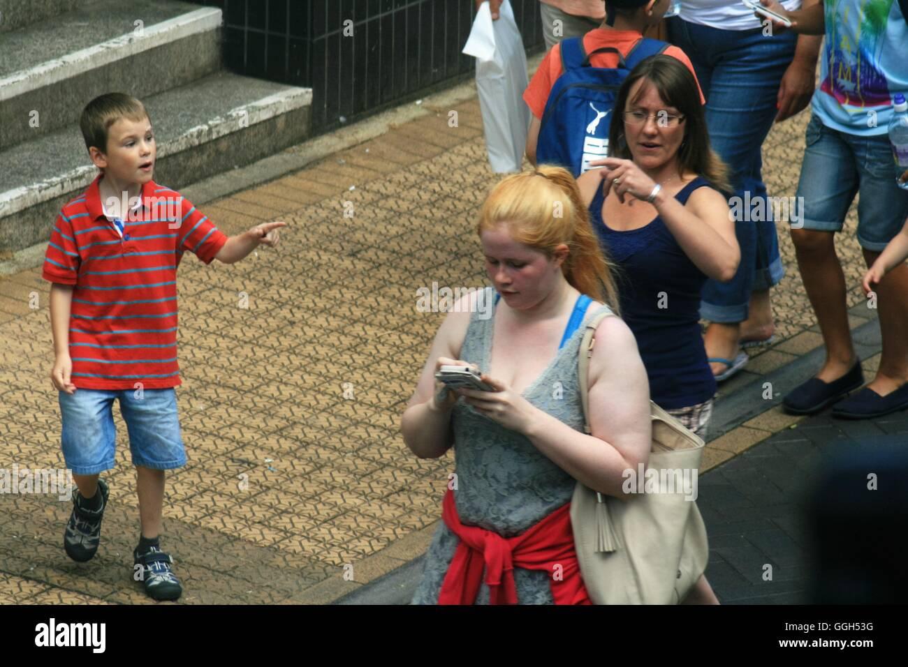 Ragazza utilizzando phone passeggiando per il centro città Immagini Stock