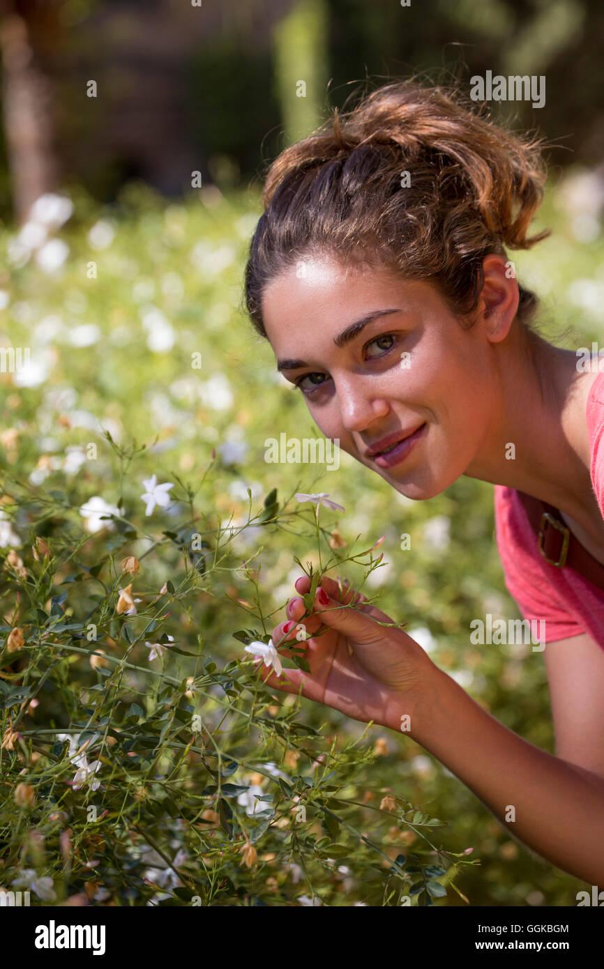 Giovane donna godendo l'odore di fragrante di fiori di gelsomino, Siviglia, Andalusia, Spagna Immagini Stock