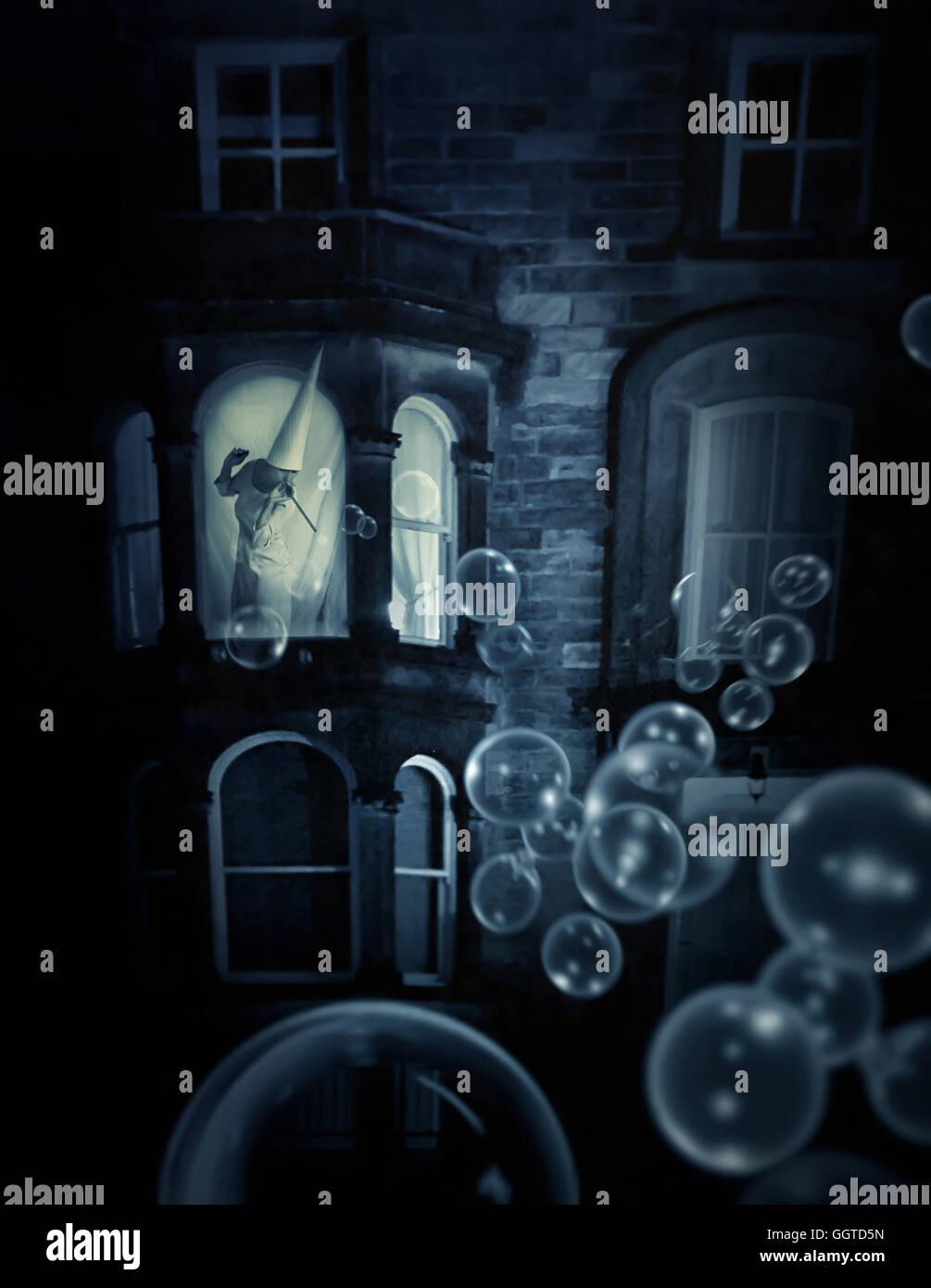 Donna che indossa il cono hat in piedi nella finestra making bolle concettuale surreale Immagini Stock