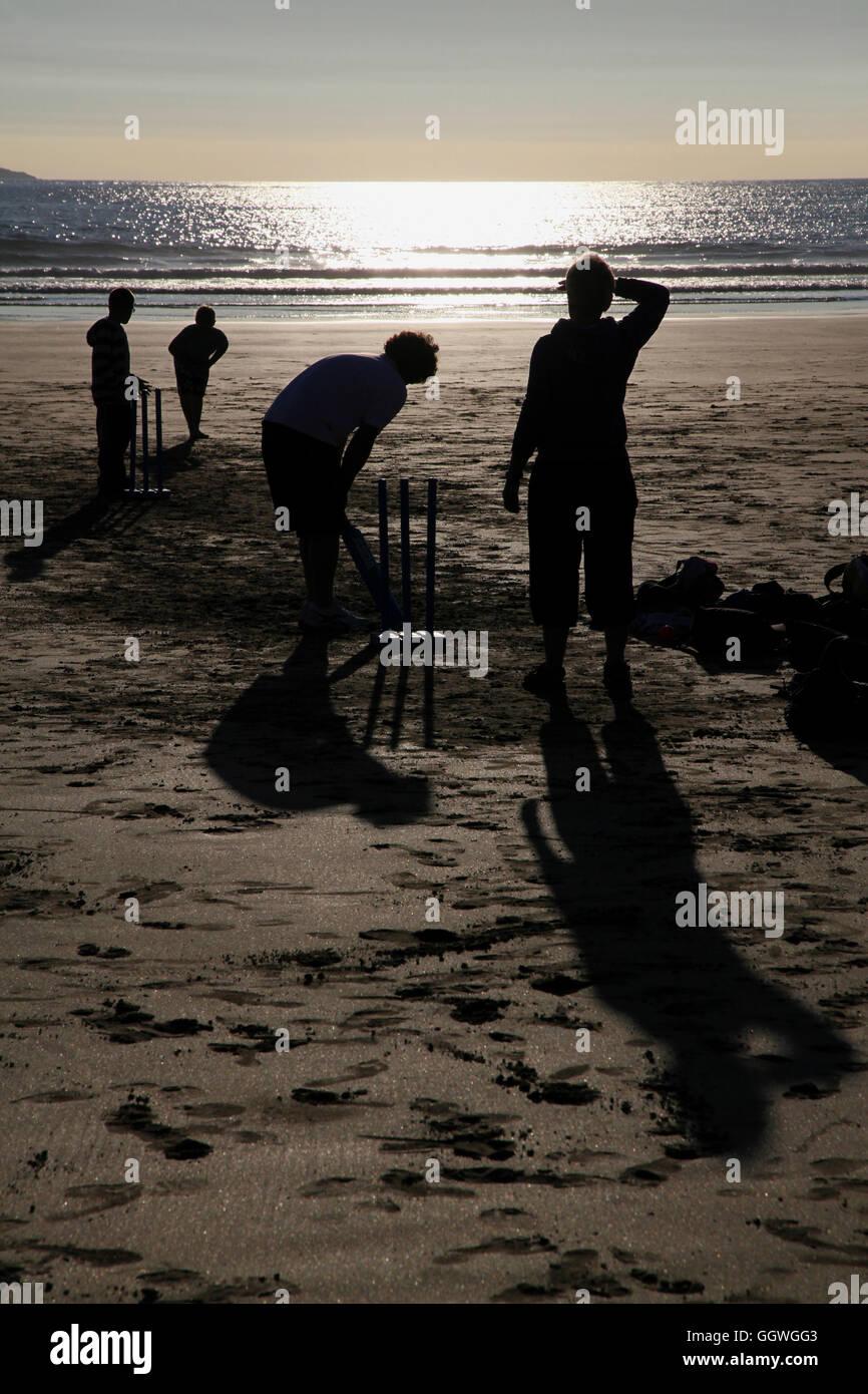 Solo su una spiaggia inglese... questi stagliano figure sta giocando la quintessenza Inglese estate gioco Cricket. Immagini Stock