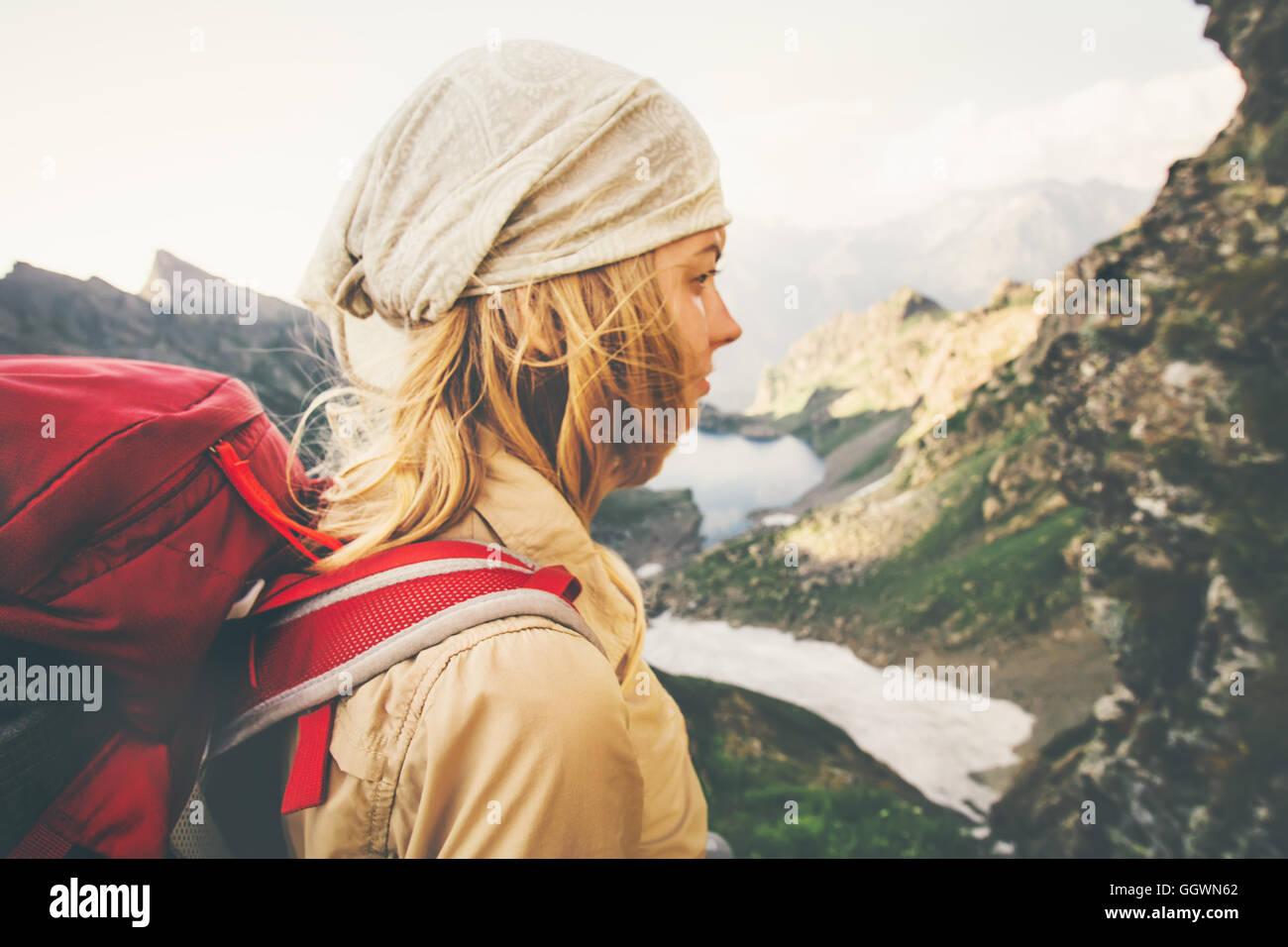 Giovane donna con zaino rosso escursionismo da soli il viaggio il concetto di stile di vita del lago e delle montagne Immagini Stock