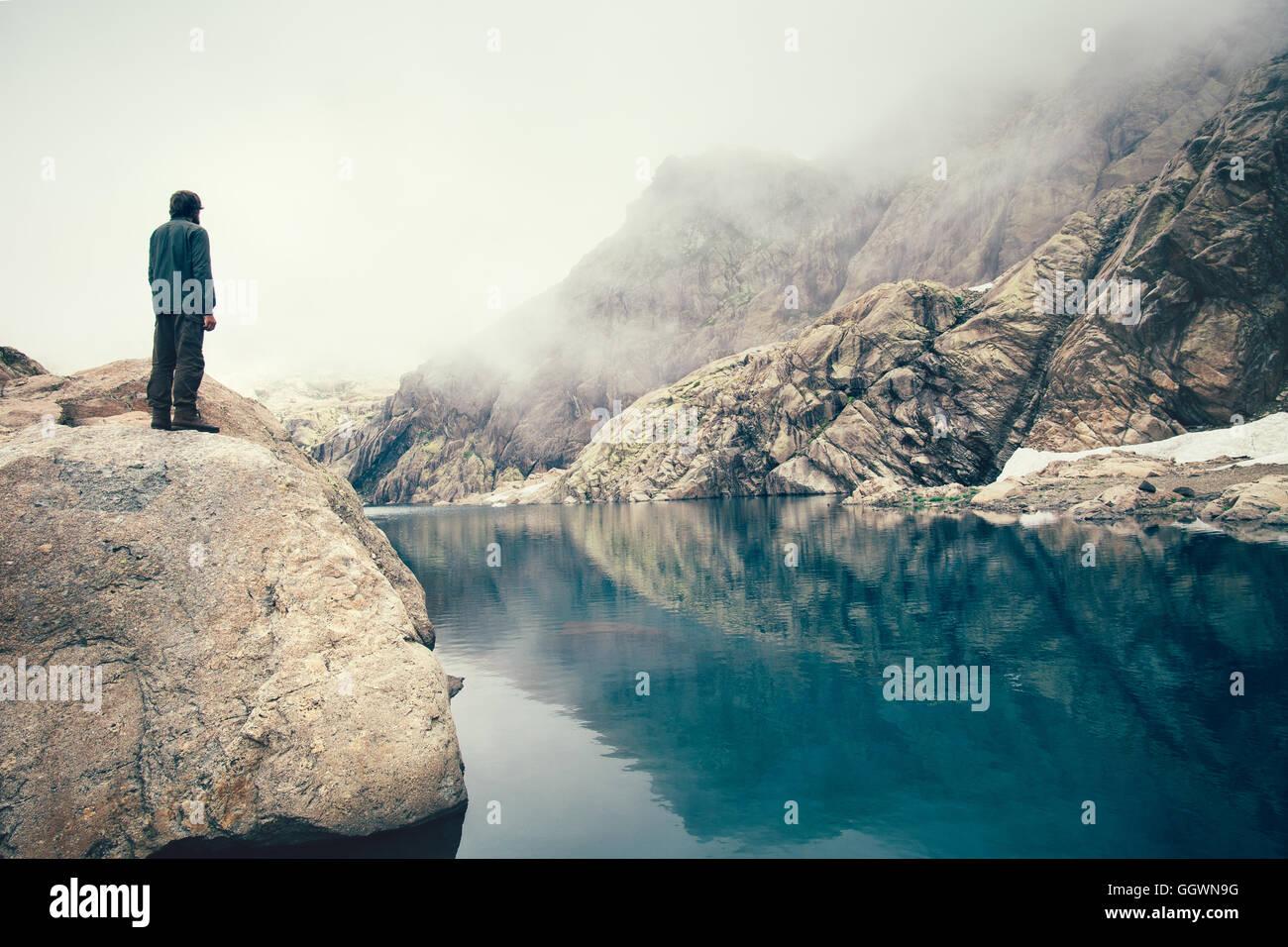 L'uomo Traveler in piedi da sola sulla scogliera di pietra lago e Misty Mountains sullo sfondo di viaggio il concetto Foto Stock