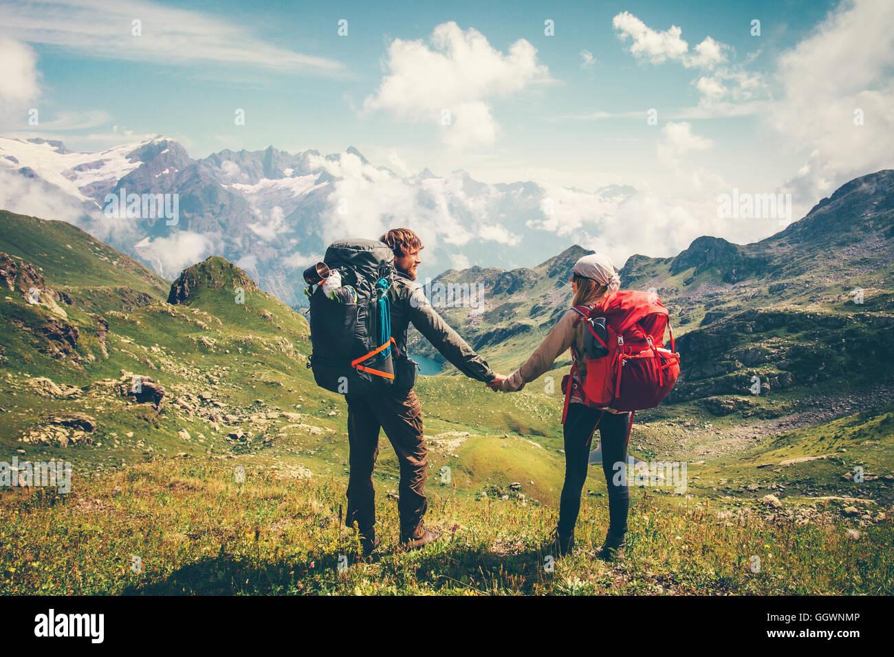 Giovane uomo e donna con zaino holding hands alpinismo Lifestyle Viaggi Vacanze estive concetto montagne e nuvole Foto Stock