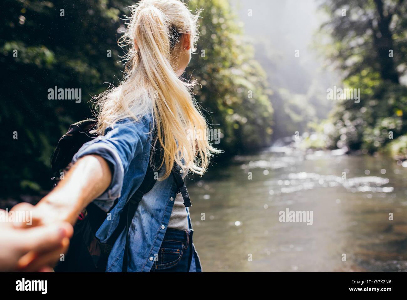 Giovane donna che conduce il suo fidanzato sulla foresta escursione. Punto di vista colpo di giovane attraversando Immagini Stock