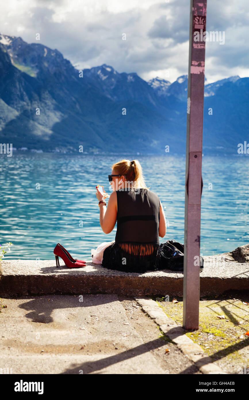 Vista posteriore di una giovane donna seduta sulla riva del lago e applicare il make up, Montreux, Canton Vaud, Immagini Stock
