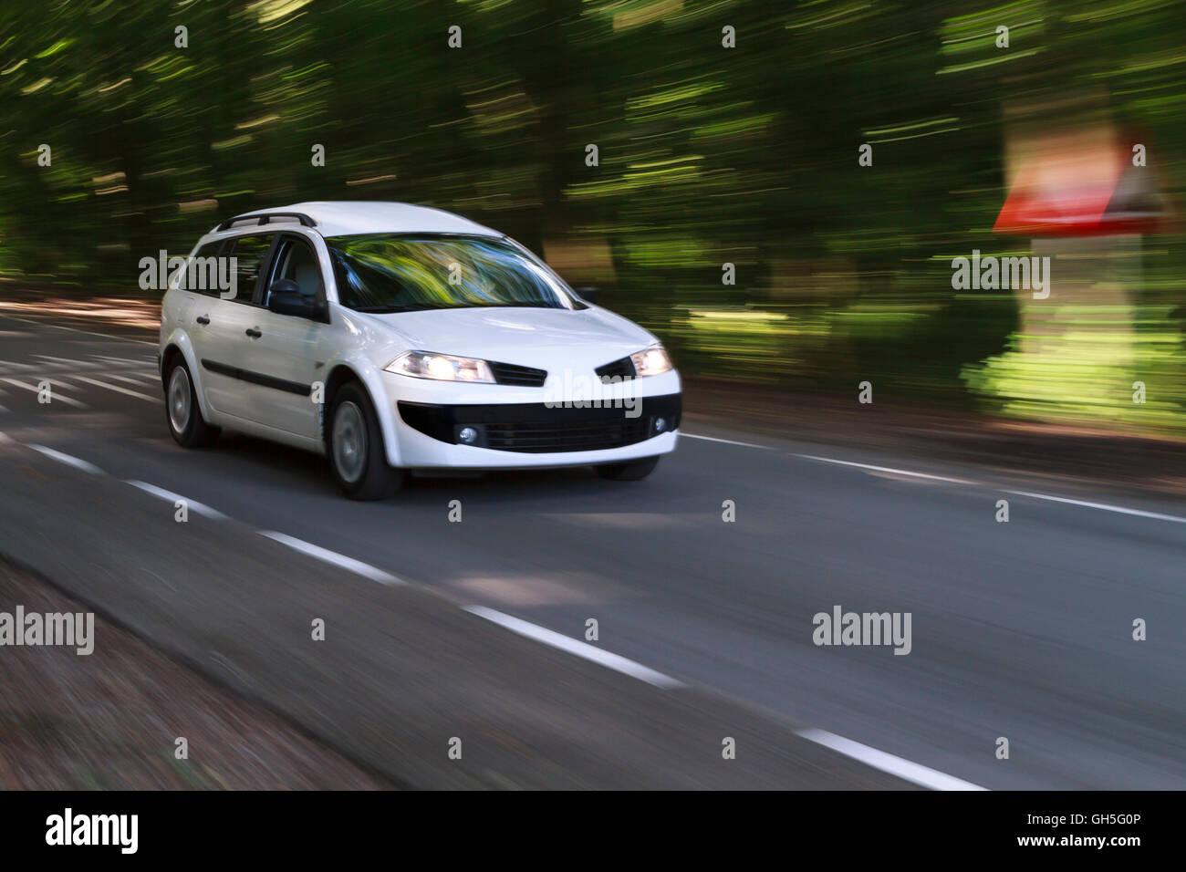 Accelerando la vettura bianca con motion guarda su una strada proveniente dalla foresta alla luce del sole Immagini Stock