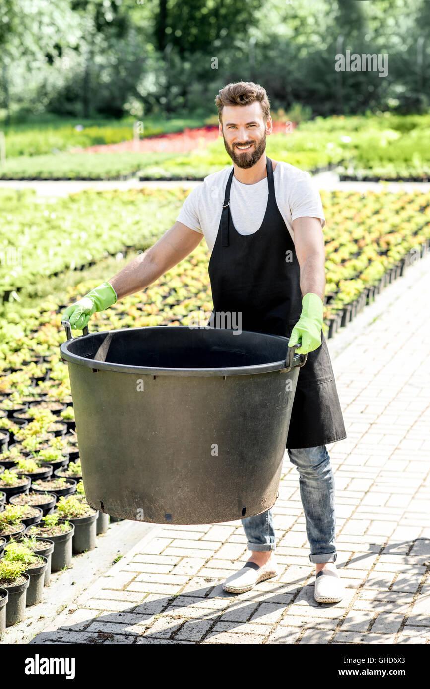 Bello il giardiniere con enorme benna Immagini Stock