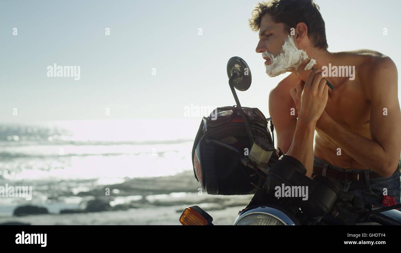 Giovane uomo su motociclo barba rasatura vicino oceano Immagini Stock