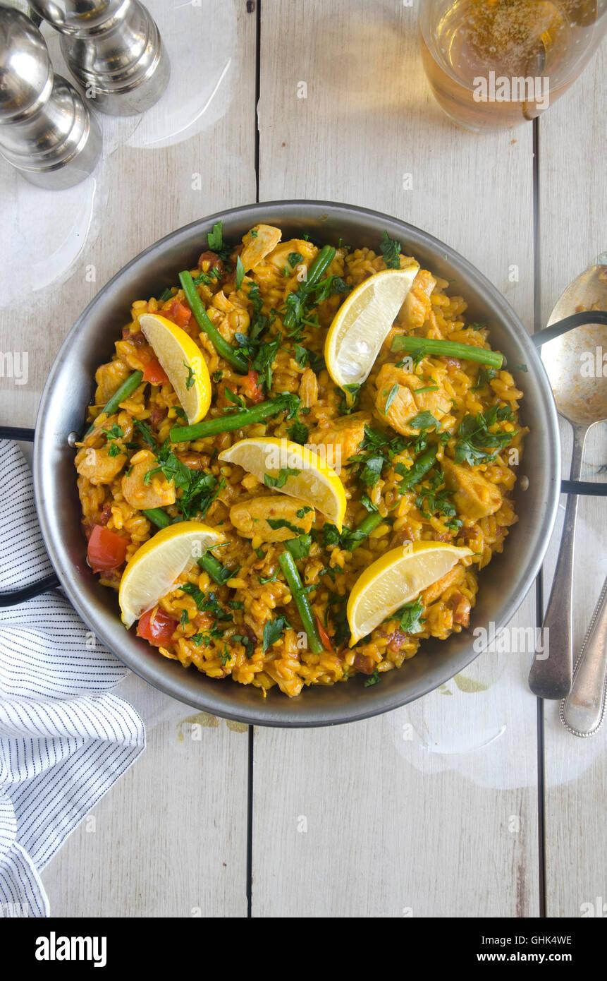 La paella spagnola con il coniglio, pomodori e fagioli verdi Immagini Stock