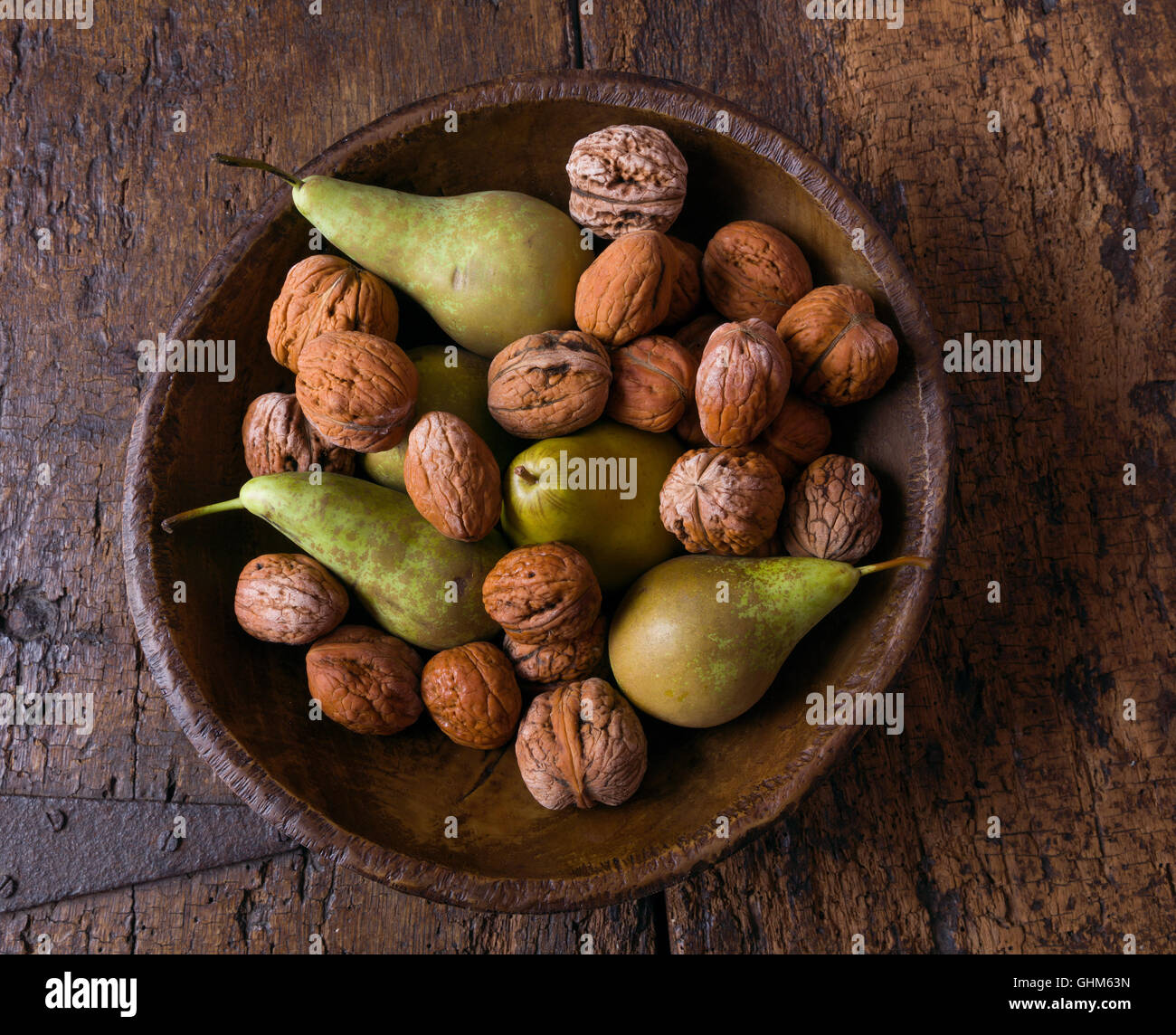 Rientrano ancora in vita con una ciotola di pere e noci su un grunge sfondo di legno Immagini Stock