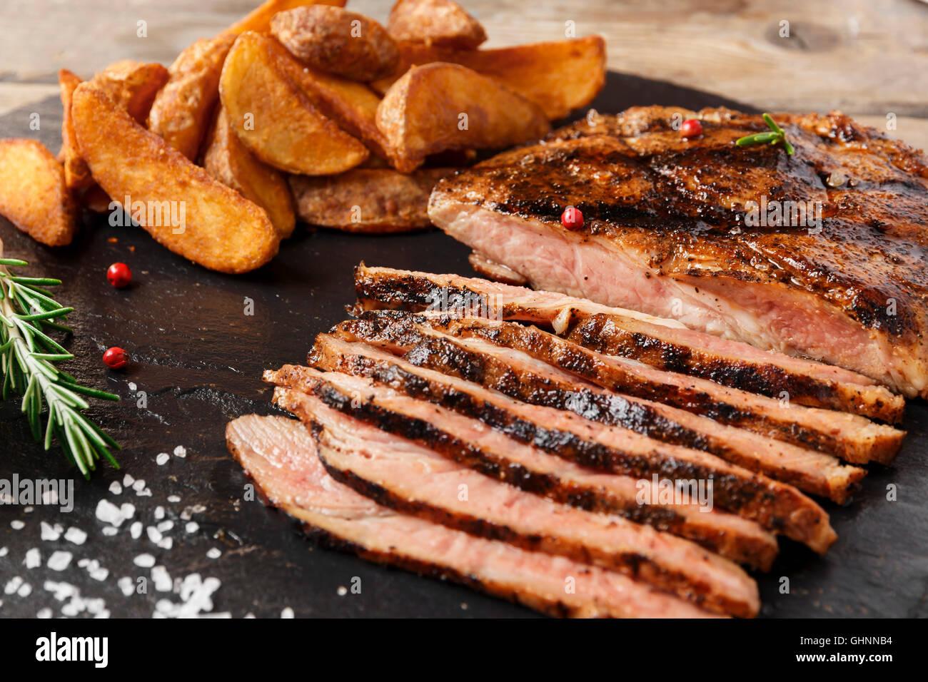 Bistecca di manzo tagliata a fette con patate al forno e salsa Immagini Stock
