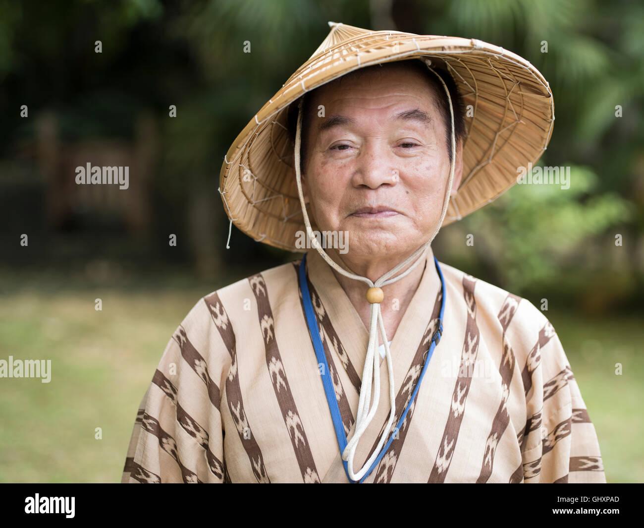 Anziani Okinawense l uomo nella sua 70's indossando il tradizionale stile bashofu kimono e cappello di paglia. Immagini Stock