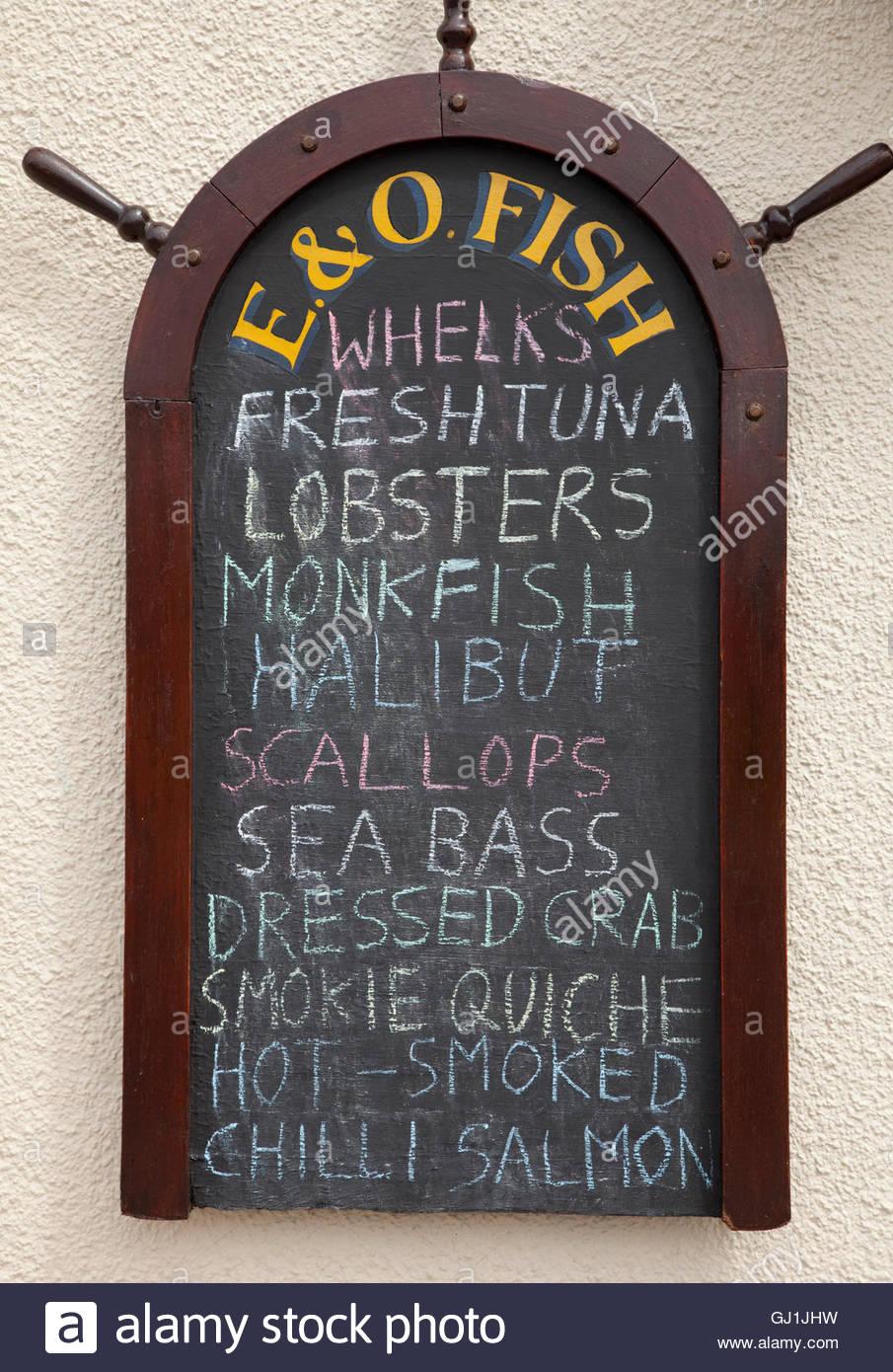 beb924e9266 Il segno della lavagna elencando i diversi tipi di pesce per la vendita in  un pescivendoli