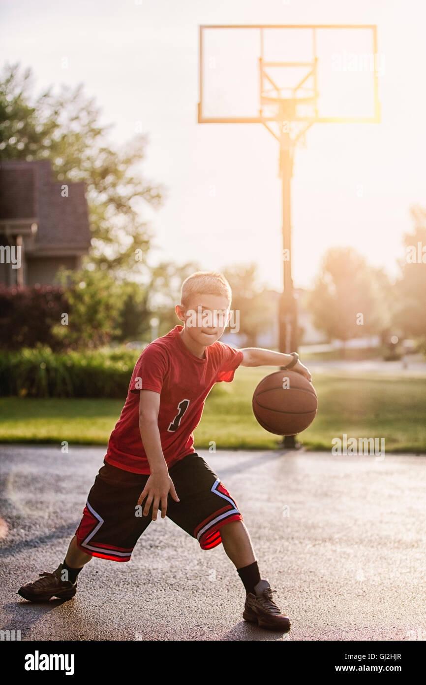 Ritratto di giovane ragazzo in dribbling con basket Immagini Stock