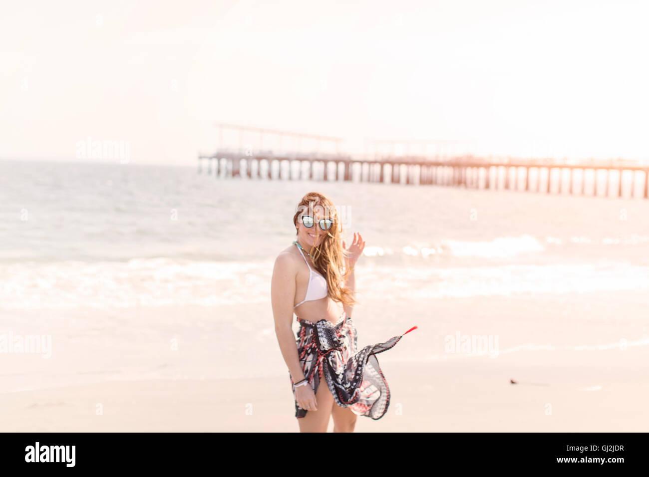 Donna che indossa sarong sulla spiaggia guardando la telecamera, Coney island, Brooklyn, New York, Stati Uniti d'America Immagini Stock