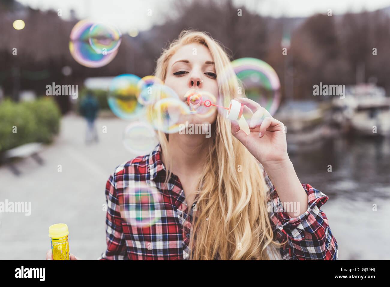 Ritratto di giovane donna sul lungomare a soffiare bolle, Lago di Como, Italia Immagini Stock