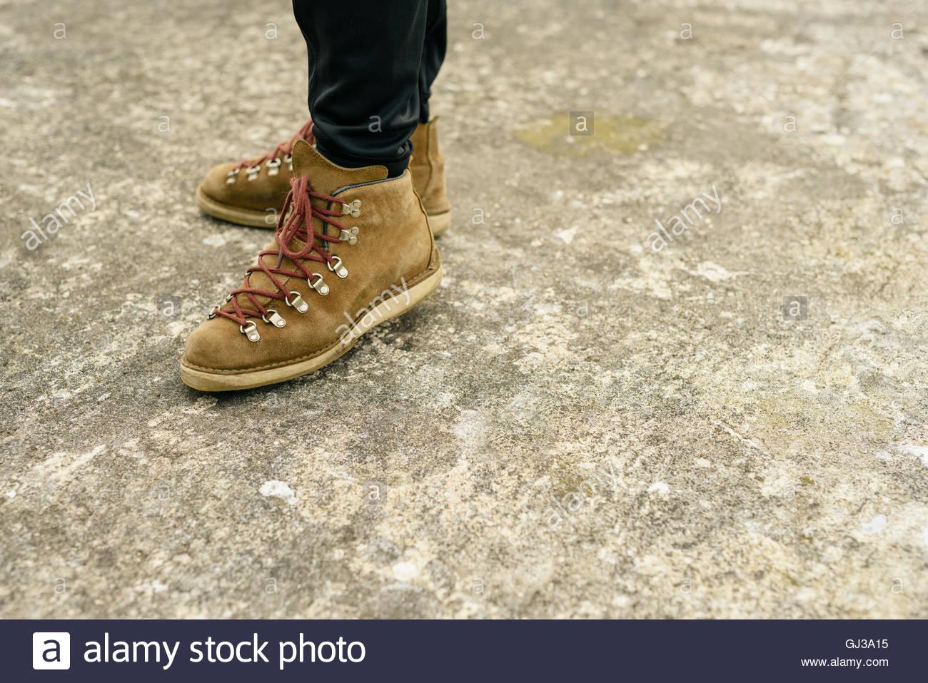 Persona che indossa scarponi permanente sulla massa di calcestruzzo Immagini Stock