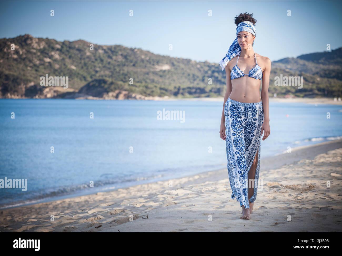 Giovane e bella donna che indossa un bikini top e sarong per passeggiare sulla spiaggia, Costa Rei, Sardegna, Italia Immagini Stock