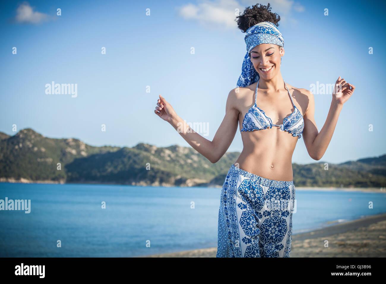 Giovane e bella donna che indossa un bikini top e sarong balli sulla spiaggia, Costa Rei, Sardegna, Italia Immagini Stock