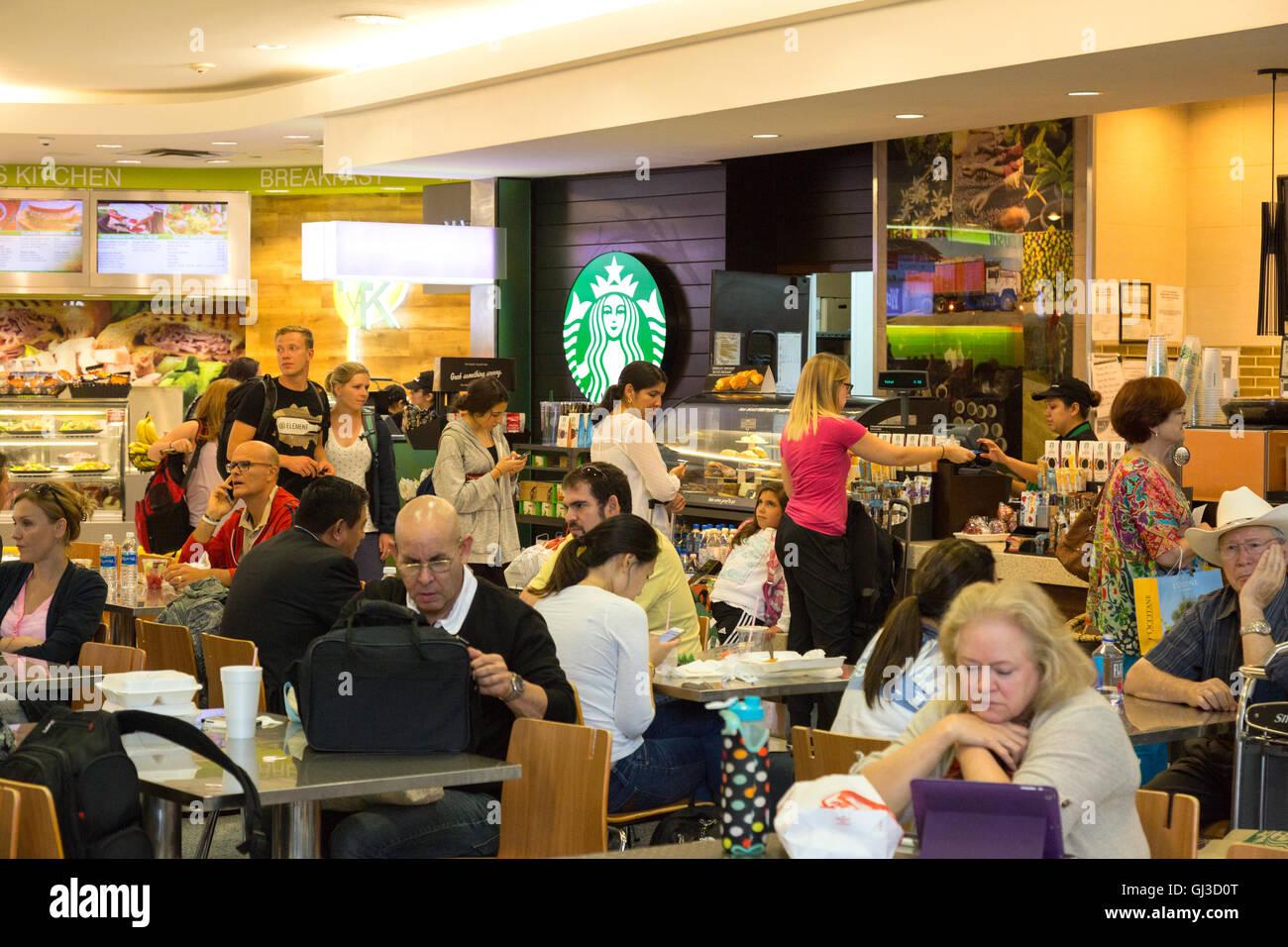 Le persone aventi il caffè in uno Starbucks Cafe, della sala partenze, terminale E George Bush Interconinental aeroporto, Houston Texas Foto Stock
