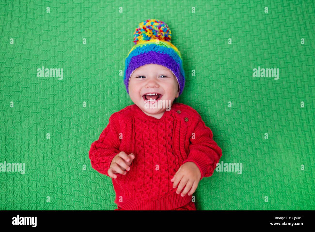 Carino baby in calda lana berretto lavorato a maglia su una coperta di  rosso. Autunno e Inverno di abbigliamento per bambini piccoli. Maglieria colorata  per ... b727cc462760