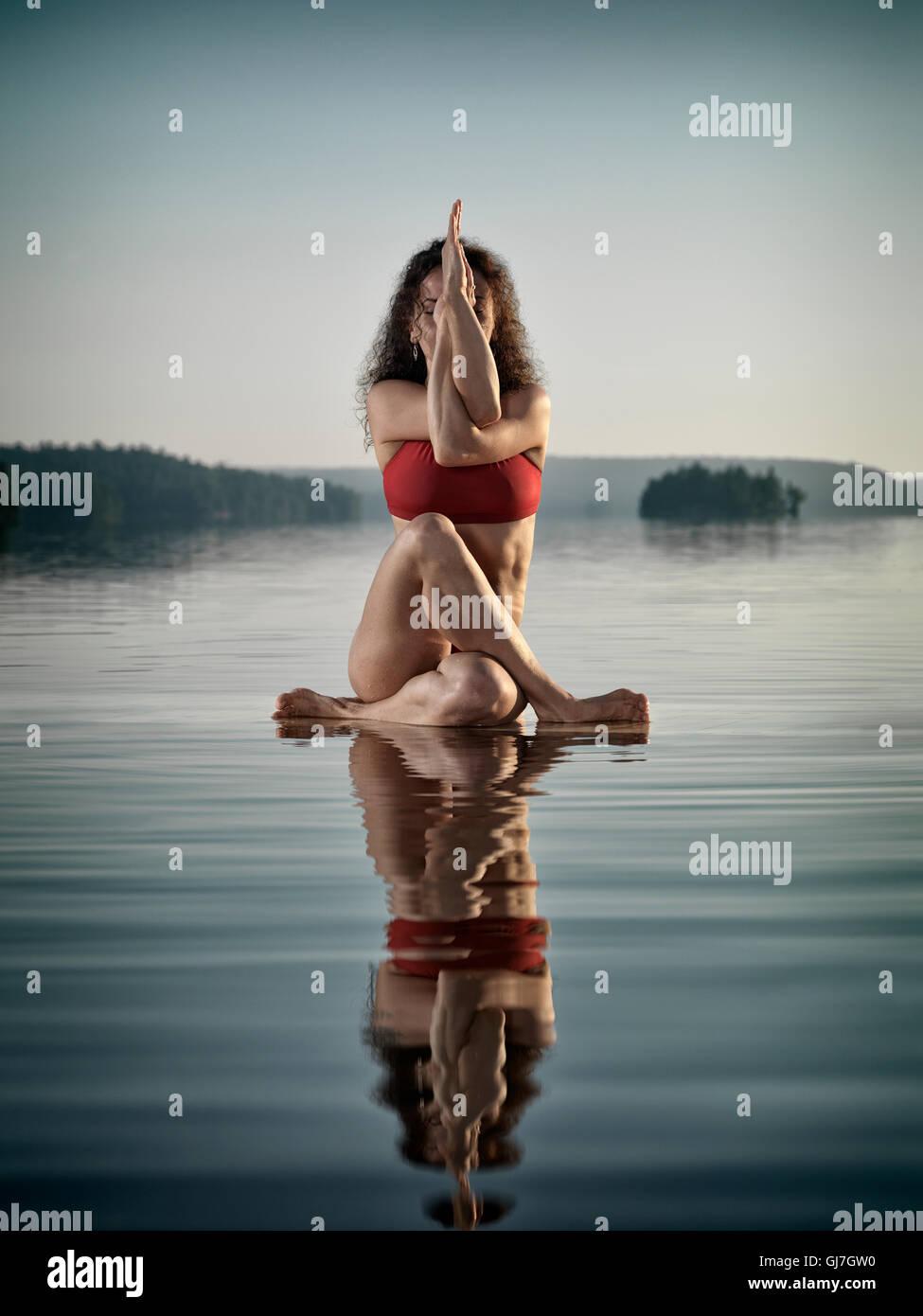 Concetto artistico di una giovane donna in costume da bagno facendo una variazione di yoga Eagle postura, Guradasana, Immagini Stock