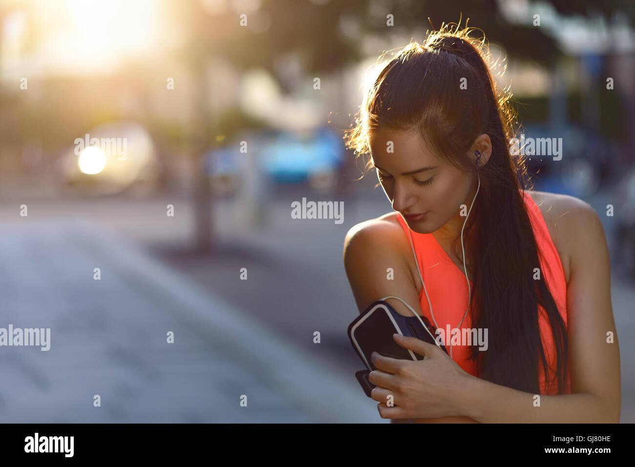 Pareggiatore donna controlla la sua musica dispositivo attaccato a un braccio band indossando vivacemente colorato Immagini Stock
