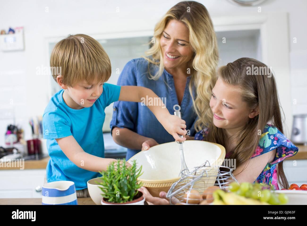 Proprietà rilasciato. Modello rilasciato. La madre e il figlio e la figlia cucina in cucina. Immagini Stock