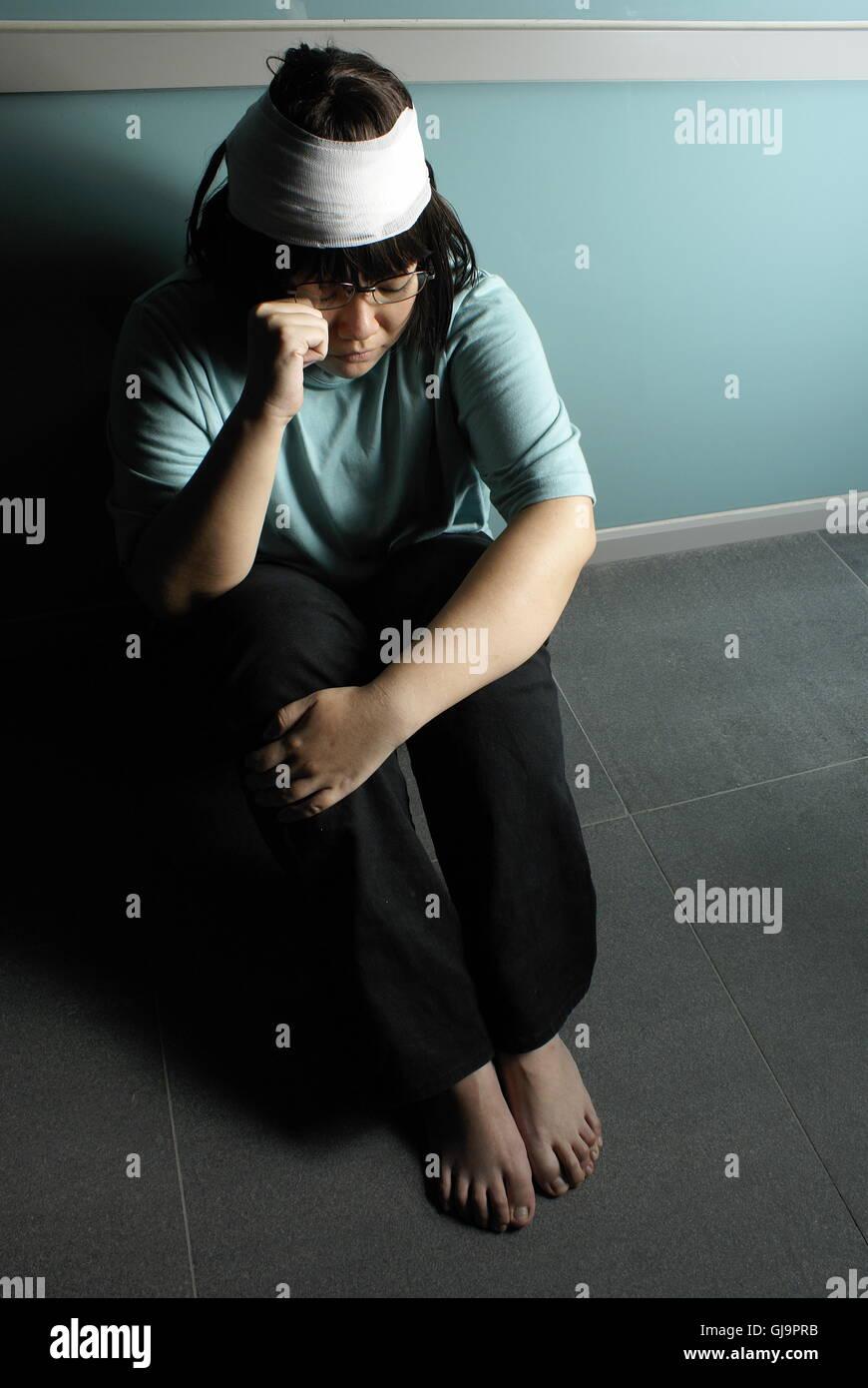 Feriti e miserabili teen ragazza infelice rannicchiato sul pavimento Foto Stock
