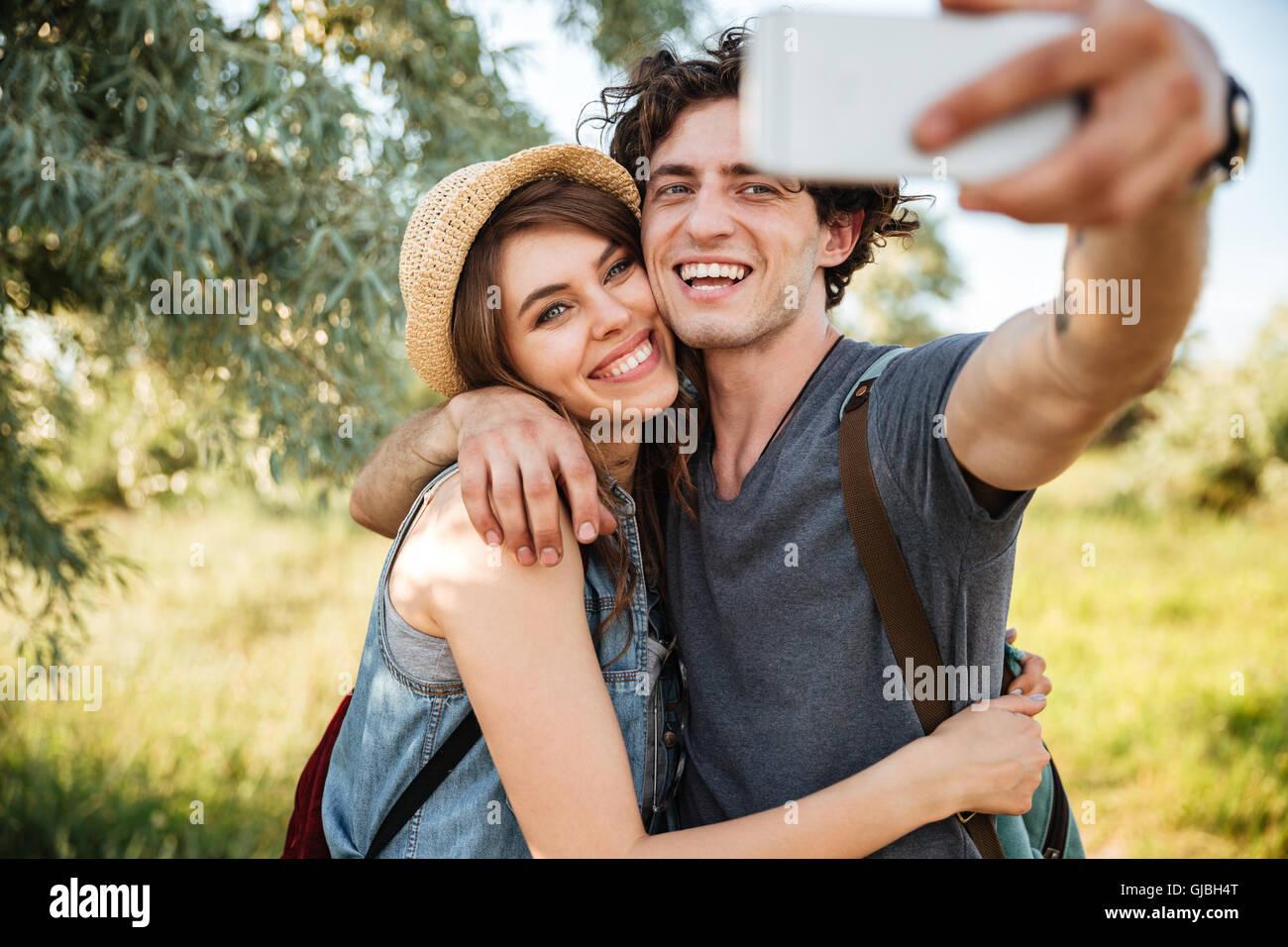 Giovani sorridendo felice coppia con zaini trekking nella foresta e rendendo selfie Foto Stock