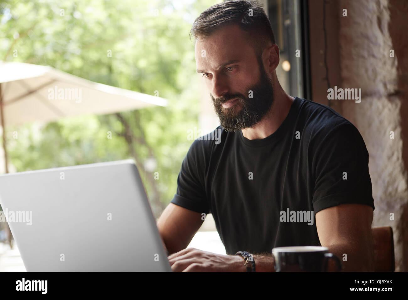 Concentrato Uomo Barbuto vestita di nero Tshirt Notebook di lavoro tavolo in legno Urban Cafe.giovane manager Notebook Immagini Stock