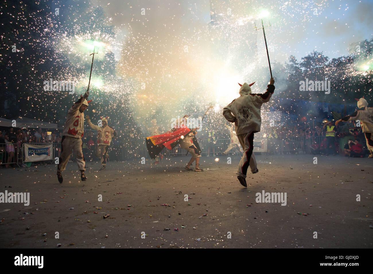 Gracia, Barcellona, Spagna. Il 15 agosto, 2016. La Festa Gracia - esecutori in costume ballando con razzi di square Immagini Stock