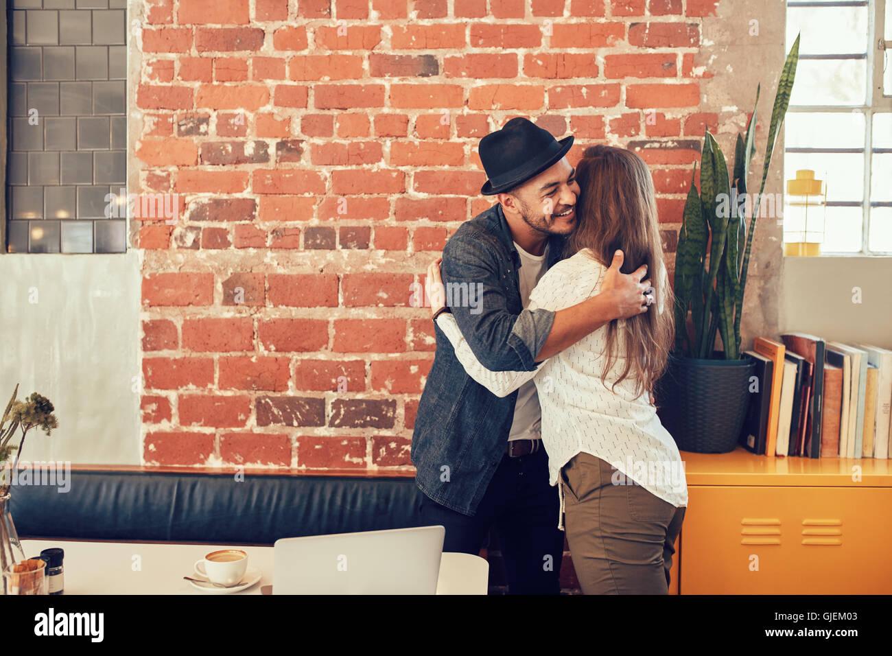 Ritratto di giovane uomo saluto una donna al cafe. Giovane uomo abbracciando la sua fidanzata a un coffee shop. Immagini Stock