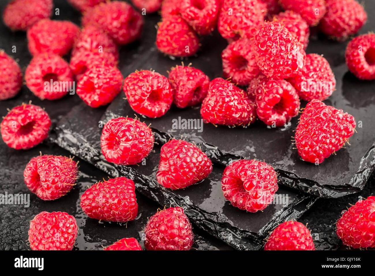 Wet lamponi rosso su nero ardesia sfondo Immagini Stock
