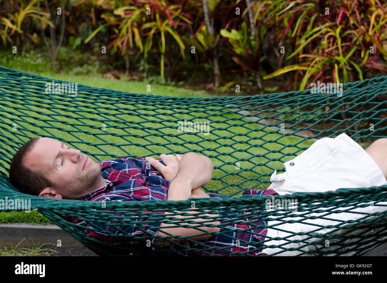 Uomo dorme in un'amaca con le braccia incrociate e gli occhi chiusi. Immagini Stock
