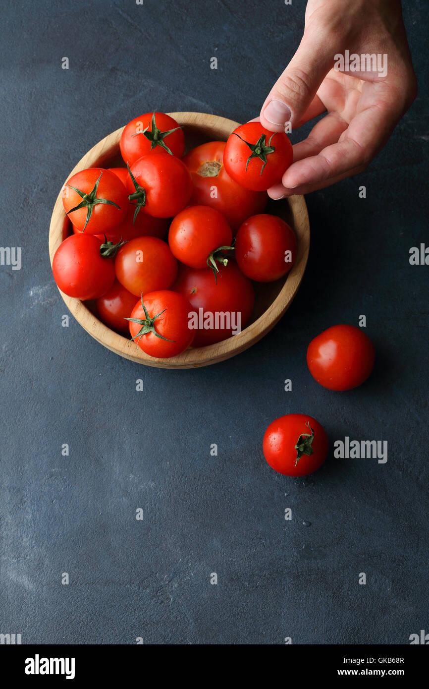 Pomodori in ciotola di legno, sfondo alimentare Immagini Stock