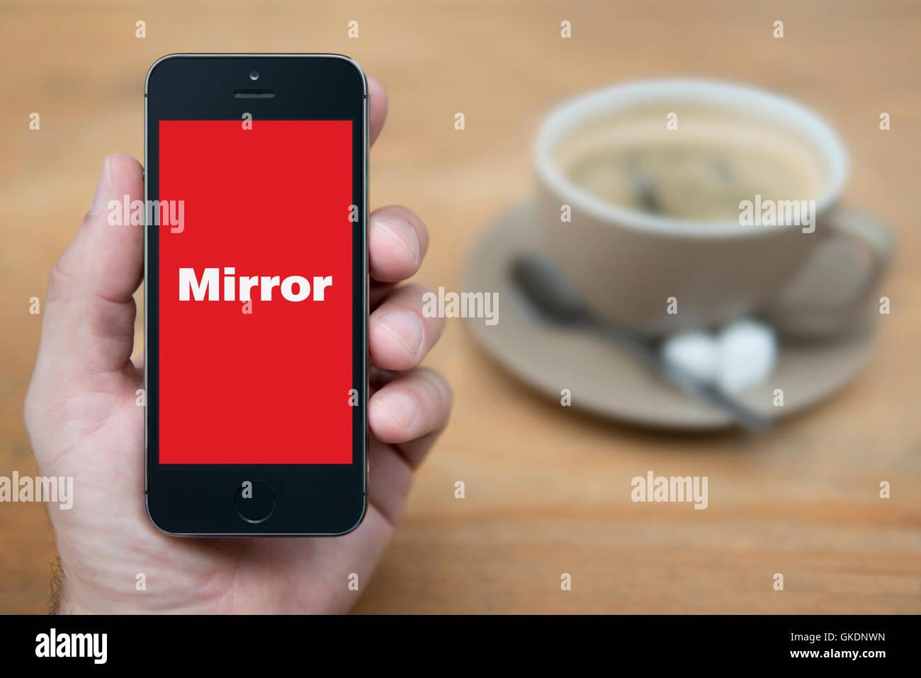 Un uomo guarda al suo iPhone che visualizza il logo a specchio, mentre sat con una tazza di caffè (solo uso Immagini Stock